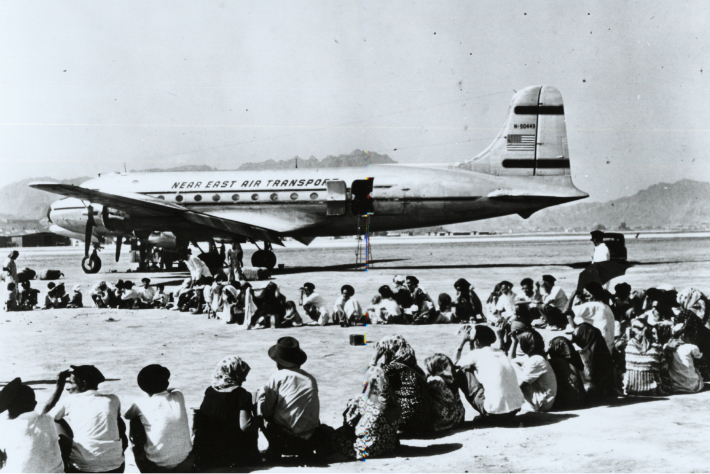 Yemenite Jews sitting on the tarmac in Yemen, waiting for JDC to airlift them to Israel during Operation Magic Carpet.