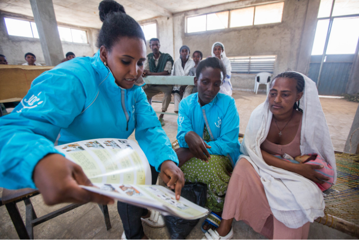 JDC volunteer presenting a chart to a female JDC client wearing a white cloth.