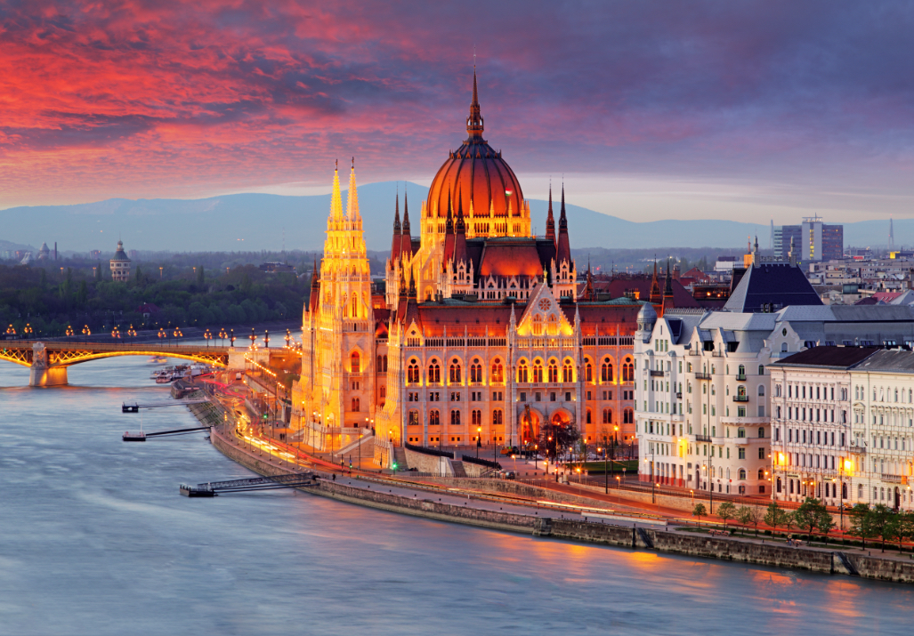 The Hungarian Parliament Building (Parliament of Budapest) in Budapest, Hungary, at dusk, next to the Danube River.