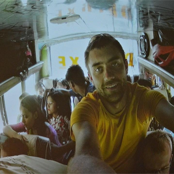 Mężczyzna pozuje do zdjęcia w autobusie. W tle pasażerowie