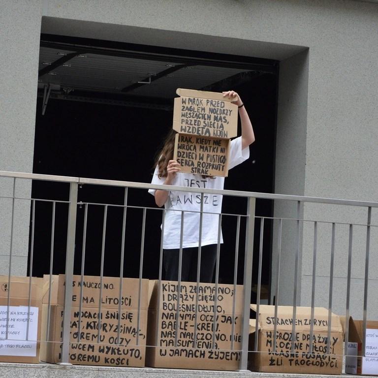 Na tarasie stoi dziewczyna, pokazuje zapisany karton. Przed nią niżej stoi kilka takich tekturowych kartonów zapisanych tekstami Krzysztofa Baczyńskiego. Ubrana jest w biała koszulkę i czarne spodnie