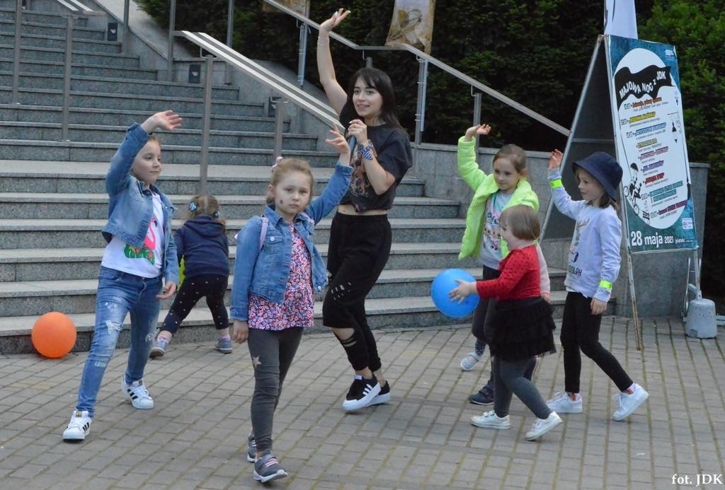 Przed budynkiem jasielskiego domu kultury tańczy młoda dziewczyna z małymi dziećmi. Ona ubrana jest na czarno, dzieci kolorowo. Wszyscy chodzą w koło