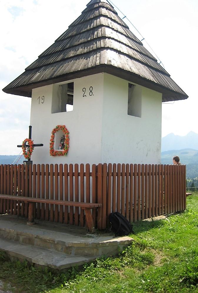 Biała kapliczka na przełęczy nad Laspszanką otoczna drewnianym płotem.