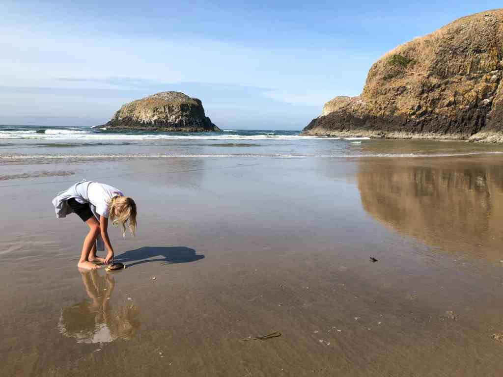 cell phone photos of girl on North Chapman Beach, Oregon Coast, with crab