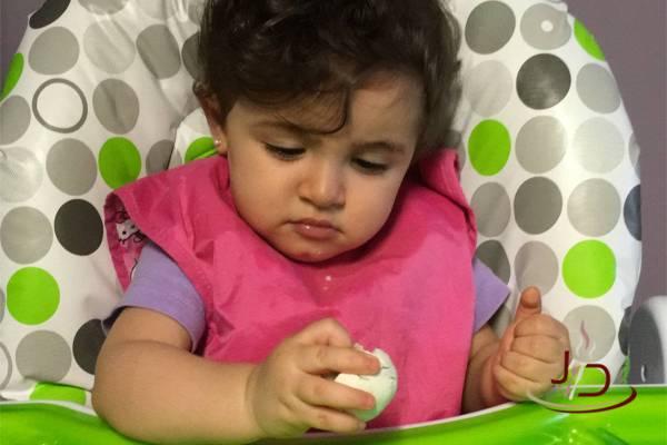 Valentina olhando para o pão de mandioca