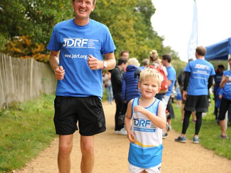 Dad and son finish running smiling looking at the camera