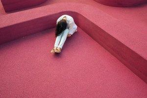Déception et découragement - FEmme assise par terre dans un décor rose la tête baissée sur ses jambes