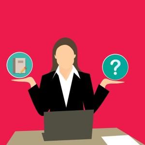 Lexique Curriculum Vitae : Femme devant son ordinateur, dans une main un cahier et dans l'autre un point d'interrogation