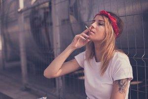 Femme rebelle : femme blonde avec un bandana rouge dans les cheveux, tatouée et fumant une cigarette