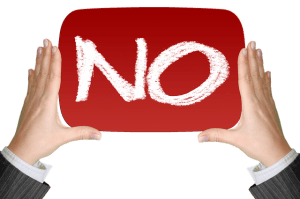 """Savoir dire non sans se sentir coupable - deux mains tenant un panneau rouge où est écrit """"no"""""""