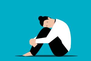 Lâcher prise, comment trouver la force ? femme brune triste assise par terre les bras autour de ses jambes