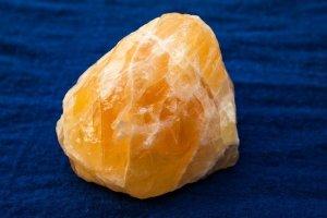 Morceau de calcite orange sur un tissu bleu foncé