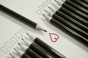 Phrases positives - un crayon à mine rouge avec lequel un coeur a été dessiné au milieu de crayons à mine noire