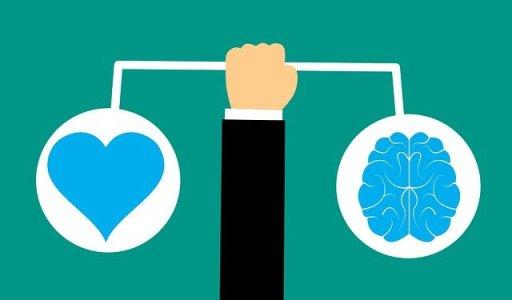 Les 20 clés pour relativiser à coup sûr - Bras d'un homme portant une balance avec un coeur et un cerveau en équilibre