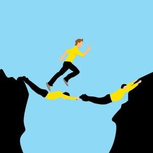 10 techniques pour relever un défi : aller trouver de l'aide - Personne passant par-dessus le vide grâce à deux personnes servant de pont.