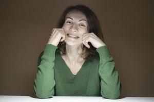 Les super-pouvoirs du sourire - un sourire forcé peut aussi destresser - Femme se forçant à sourir en tirant sur ses joues