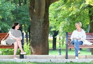 Deux femmes assises chacune sur un banc en train de discuter