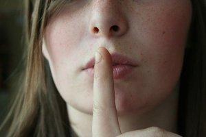 Femme le doigt sur la bouche invitant à se taire