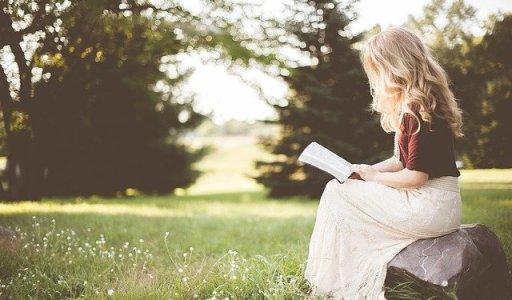 Timide ou introverti -les différences - Jeune femme blonde en train de lire dehors assise sur un rocher.