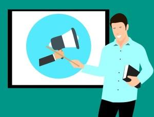 Timide ou introverti : les différences - l'introverti peut prendre la parole en public - Homme montrant un mégaphone  sur un écran à l'aide d'une baguette