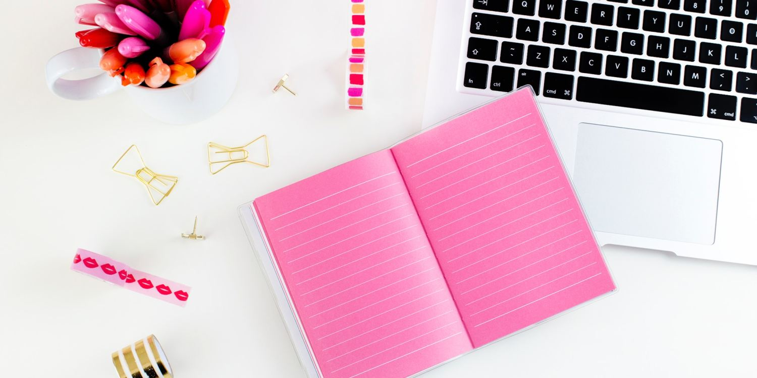 White desk, MacBook, pink notebook, and pink pens