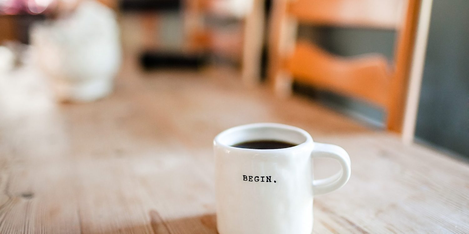Coffee cup on wooden table with BEGIN written on it.