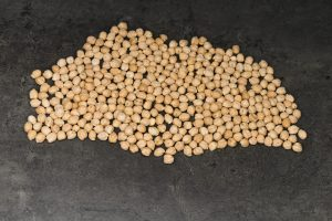 Chickpeas laid out on a dark surface.