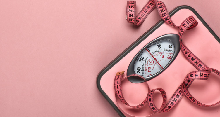 Pink scale and measuring tape on a pink background
