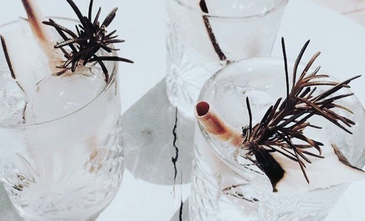 three crystal glasses with water and rosemary.