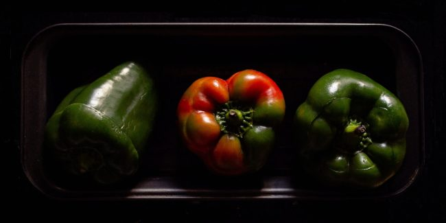 a red bell pepper with a green bell pepper on each side in a glass dish.