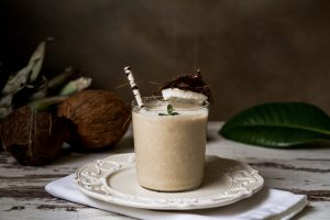 Light brown coffee smoothie in a short clear glass with a brown paper straw on a white plate.