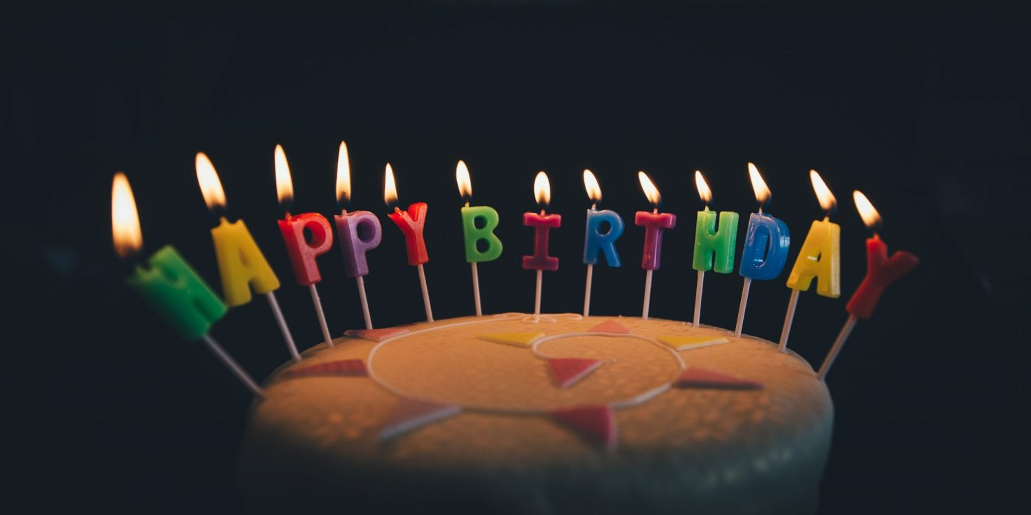 Chocolate cake with Happy Birthday candles in a half circle on a black background.