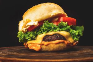 A burger with lettuce, tomato, and cheese on a dark cutting board.