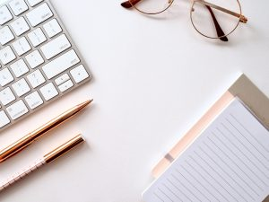 A white desk with a silver (apple) keybaord, one pink and one white note pad, rose gold pens, and glasses.