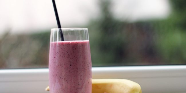 A pink colored smoothie on the counter next to raspberries and a banana.