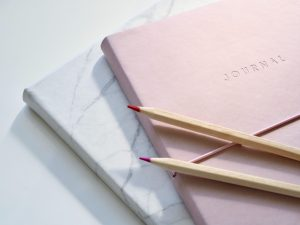A pink bound journal on top of a white marble bound journal with a white background.