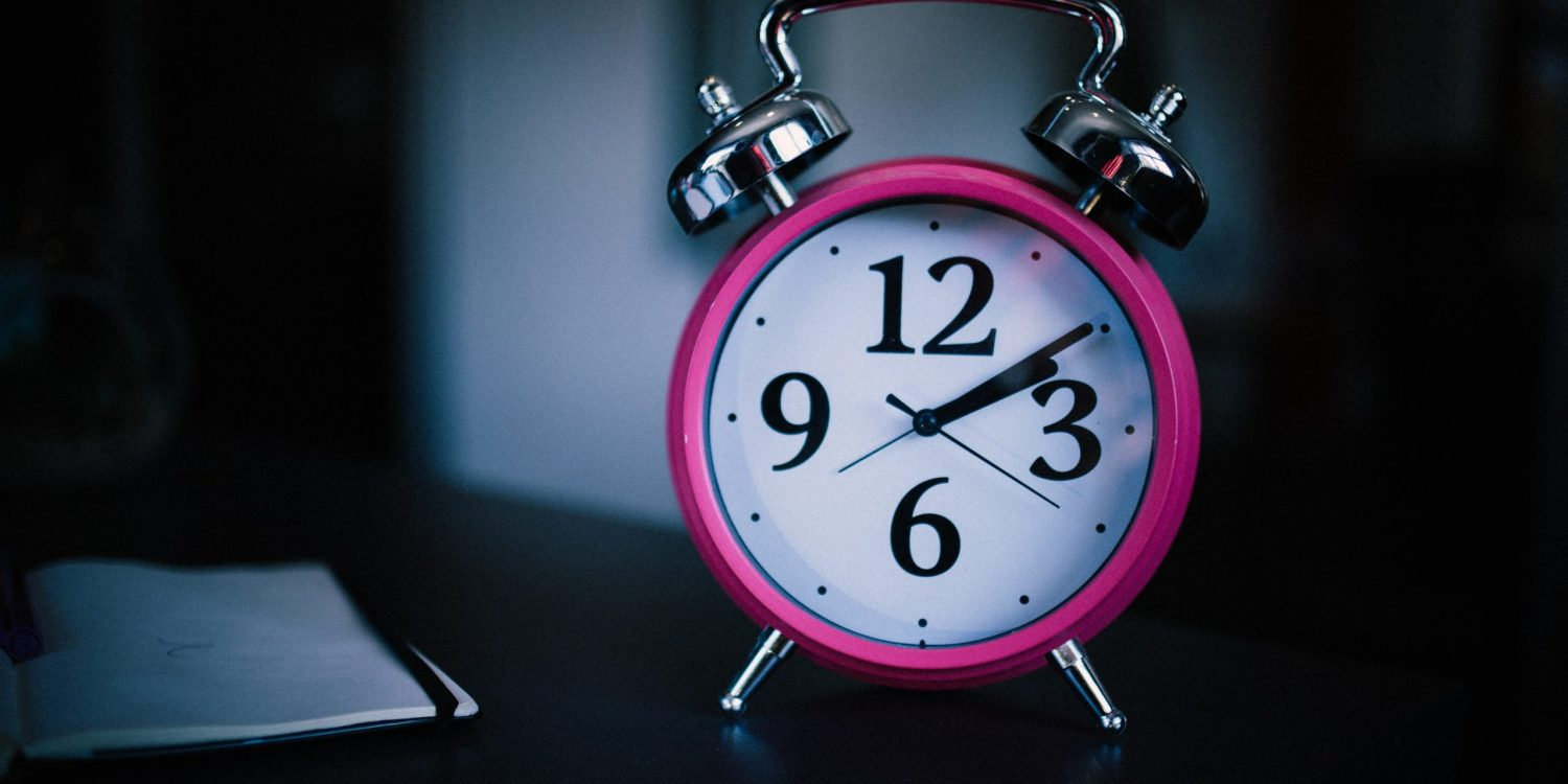 A pink old fashioned alarm clock on a dark table.