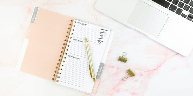 Pink planner with a gold pen and silver MacBook on pink marble background.