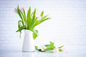 White vase with pink tulips on a white counter.