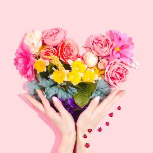 Flowers making a heart with hands holding it up on a pink back ground.