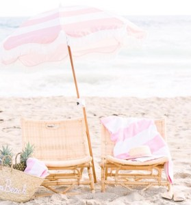 Two beach chairs under a pink and white umbrella on the beach.