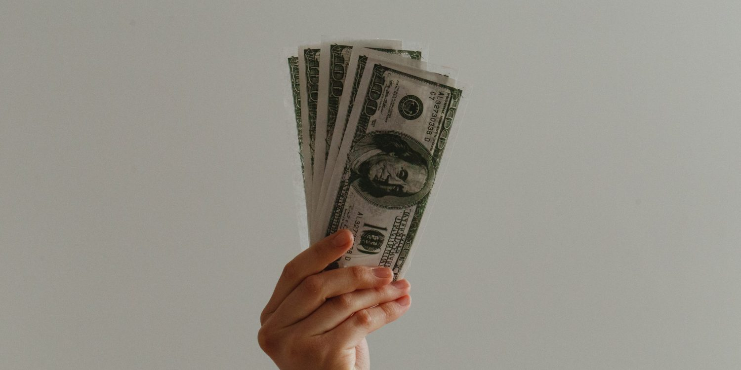 Person holding a stack of money with a white background.