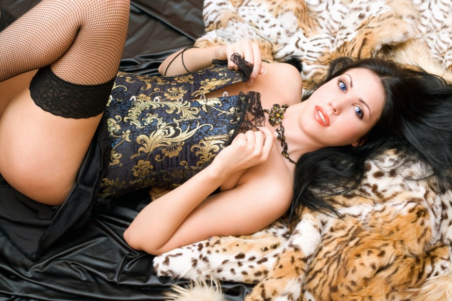 Playful young woman in a corset posing on fur