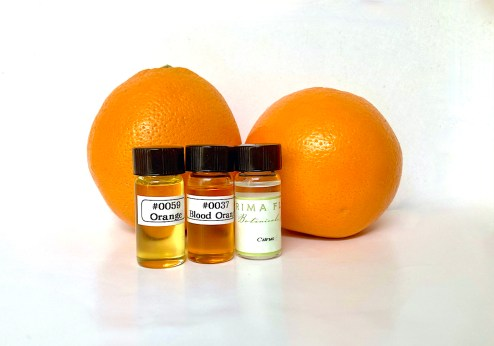 Shows the color of orange oil and blood orange oil with the fruit.