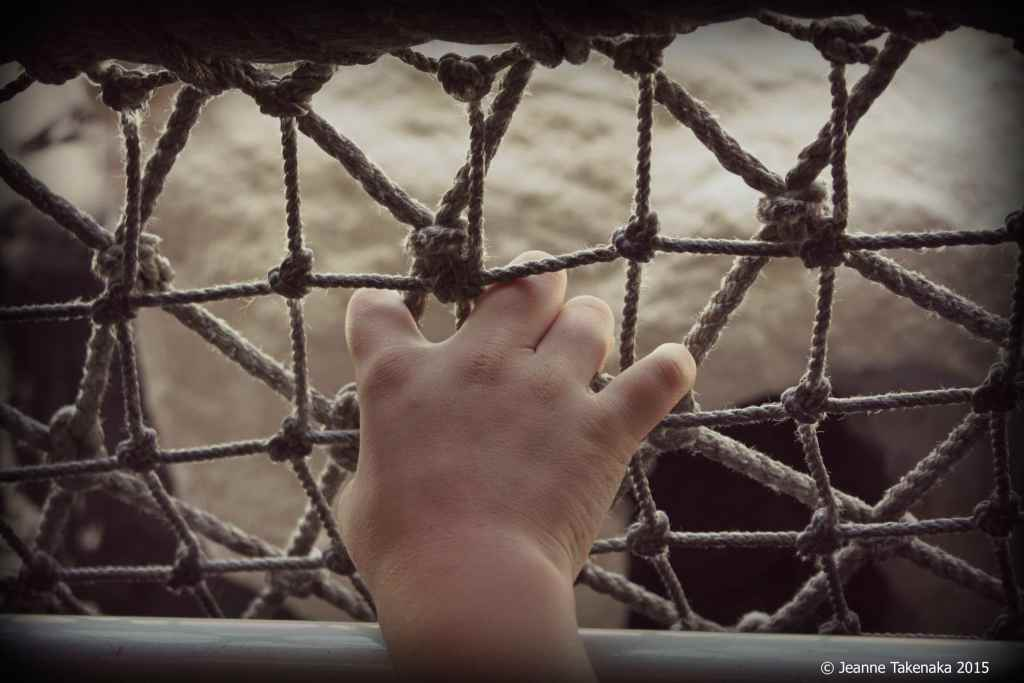 A small hand holding onto a roped fence, symbolic of how sometimes we look at what we think will give us worth, but we can't get to it