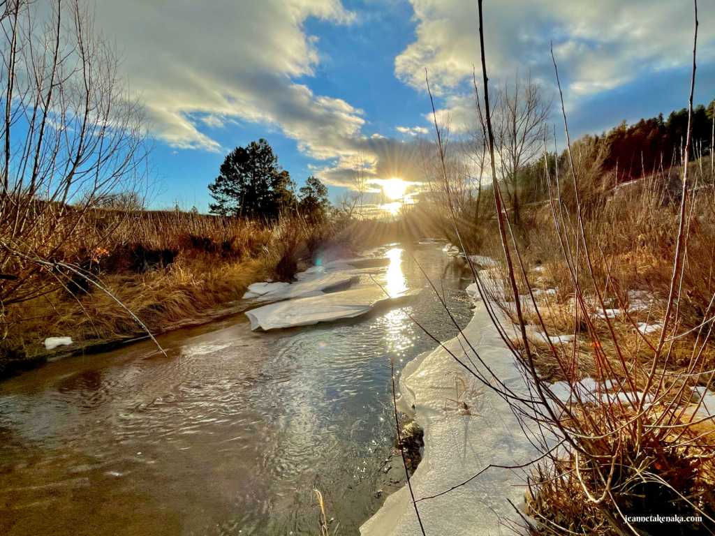 The sun peeking out from beneath a cloud and shining on a creek; a reminder that we can shine the light of Jesus in us in the face of fear