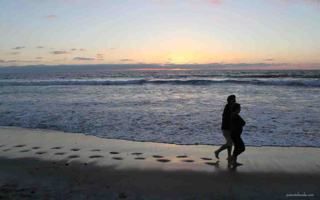 A husband and wife walking on the beach just after sunset . . . to love a husband well? Spend time together