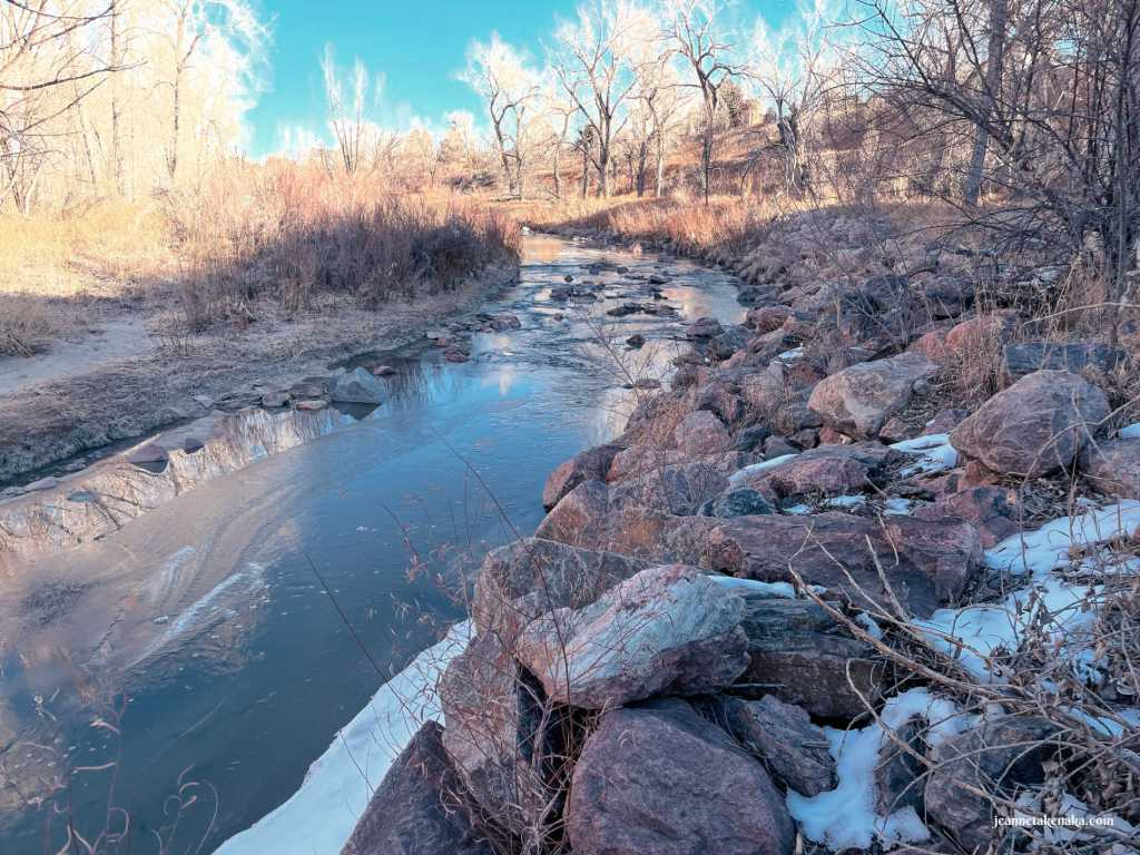 A creek with some ice and some water with trees on each bank and blue sky above, a reminder that even when trusting God is hard, He still shows up