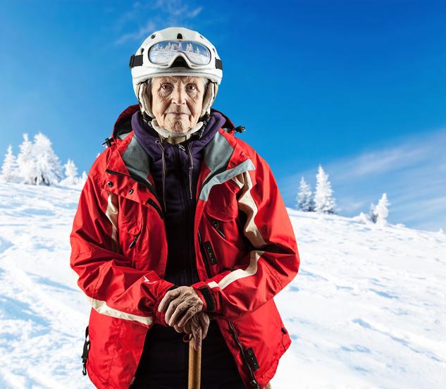 Une skieuse senior sur une piste enneigé.