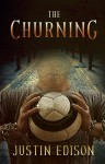 "Figure in chains holding a soccer ball before a cobblestone road, cover for ""The Churning"""